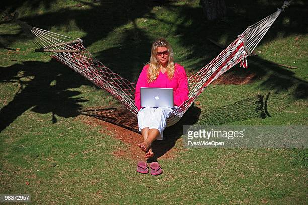 Woman sitting in a hammock and working with a notebook on January 12 2010 in Varkala near Trivandrum Kerala India