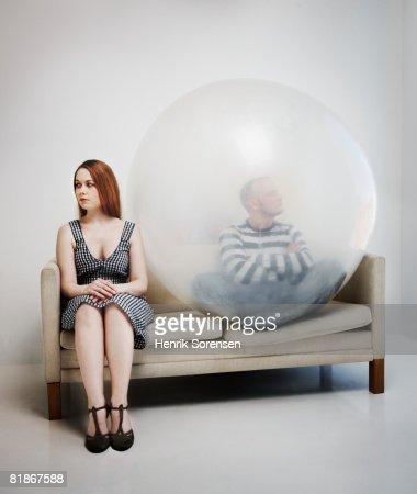 Woman sitting in a sofa with a man inside a ballon.