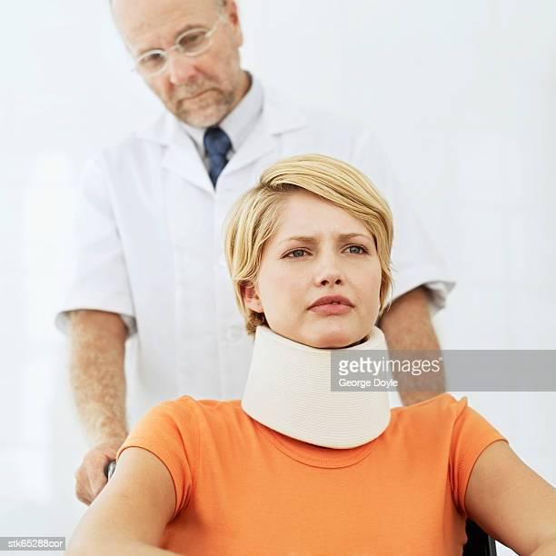 woman sitting in a wheelchair wearing a neck brace