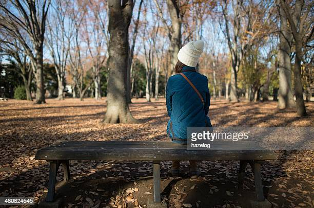 Woman sitting in a winter park on a wooden bench