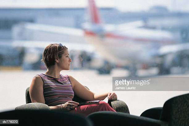 Woman Sitting in an Airport Lounge With a Magazine
