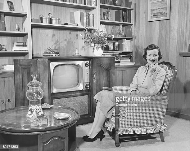 Woman sitting in armchair in living room, (B&W), portrait