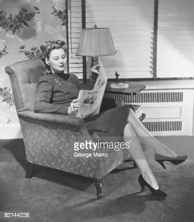 Woman sitting in armchair reading newspaper stock photo for Sitting in armchair