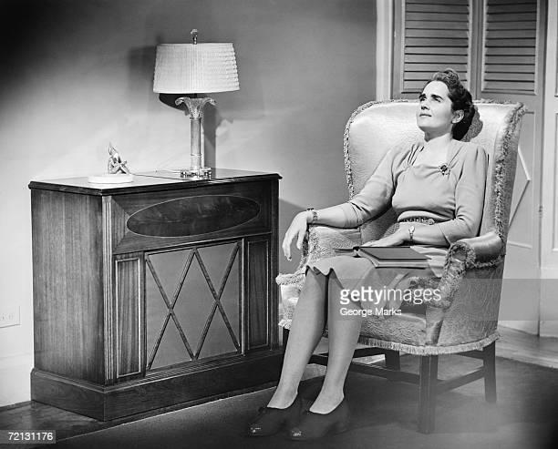 Frau sitzt im Sessel mit einem Buch auf den Knien (B & W