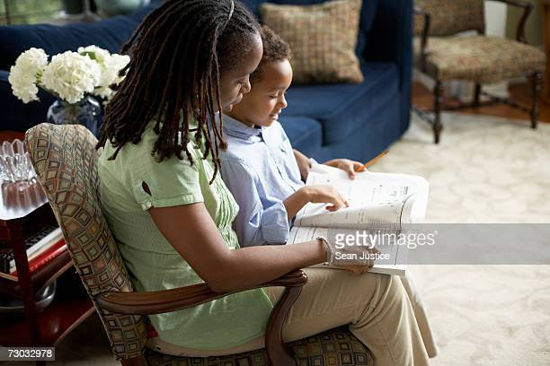 Woman sitting in armchair with son (4-5) reading book, elevated view