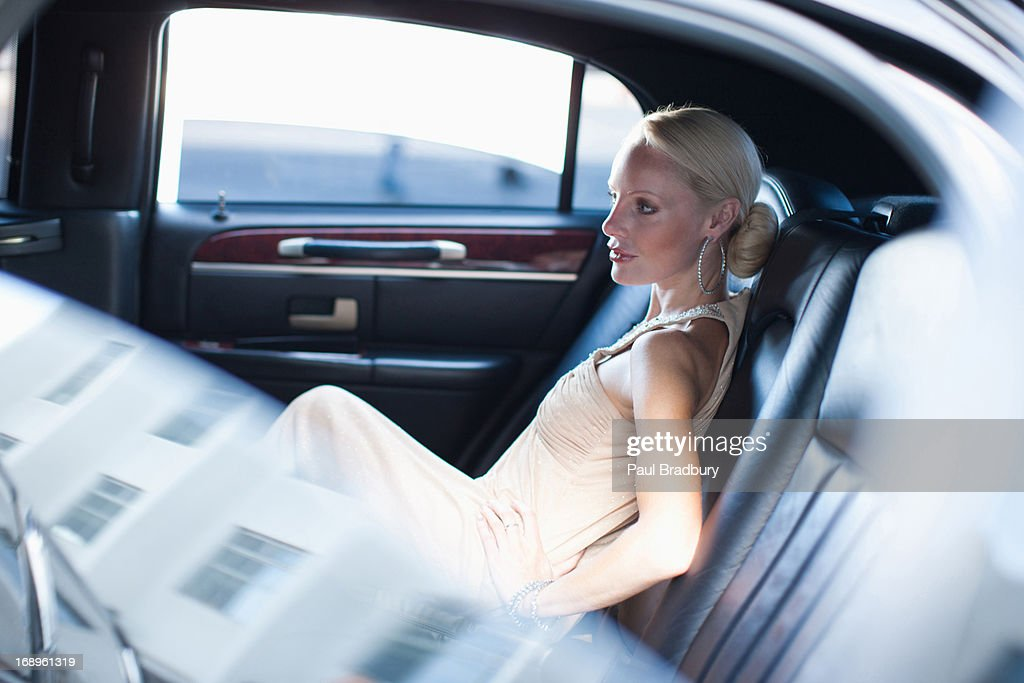 Woman sitting in backseat of limo : Stock Photo