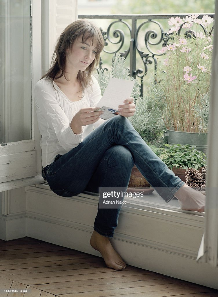 Woman Sitting In Balcony Window Reading Letter Stock Photo