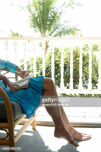 Woman sitting in bamboo chair reading on balcony, low section