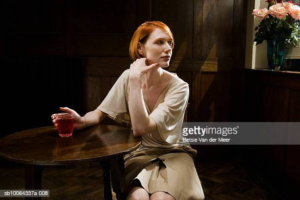 Woman sitting in bar with wine glass, looking away