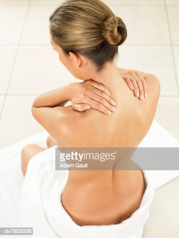Woman Sitting in Bathroom Massaging Her Neck : Stockfoto