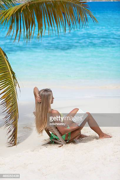 woman sitting in beach chair and reading a book