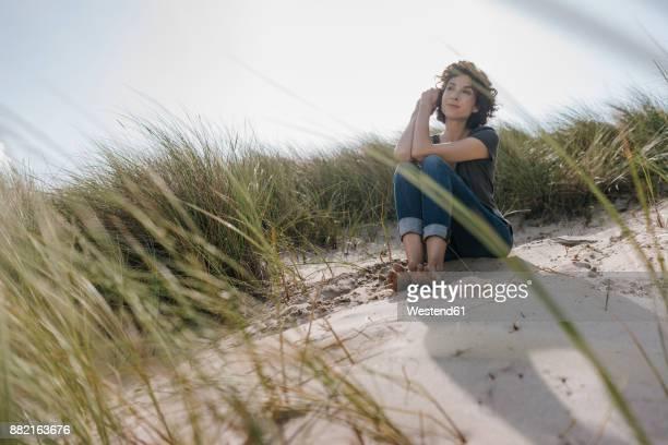 Woman sitting in beach dune