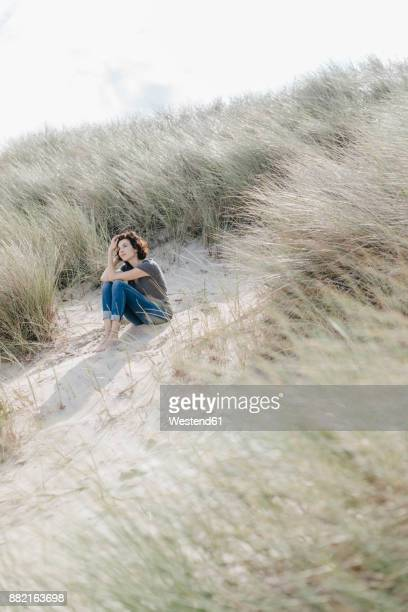Woman sitting in beach dune