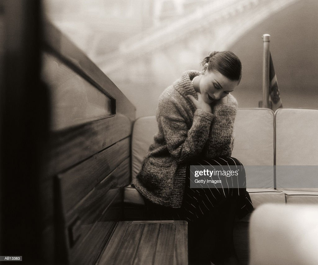 Woman sitting in boat, (B&W) : Stock Photo