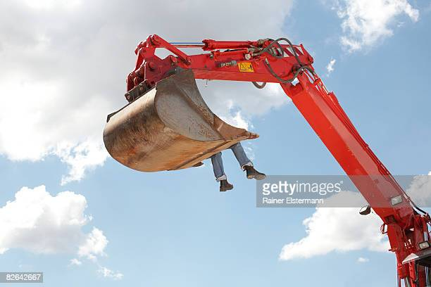 Woman sitting in bucket of earth mover