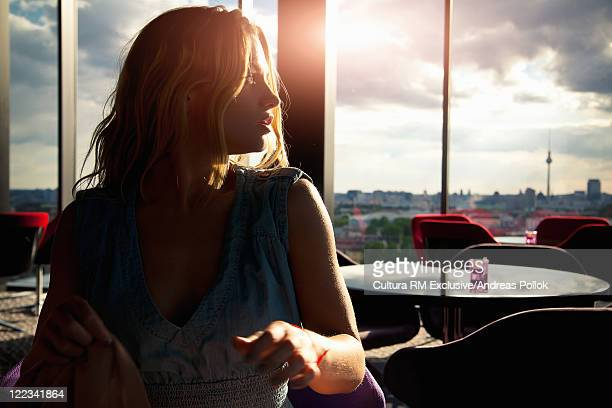 Woman sitting in cafe at sunset