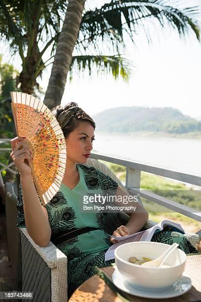 Woman sitting in cafe holding fan
