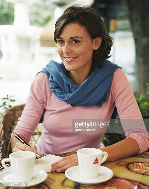 Woman sitting in cafe, smiling