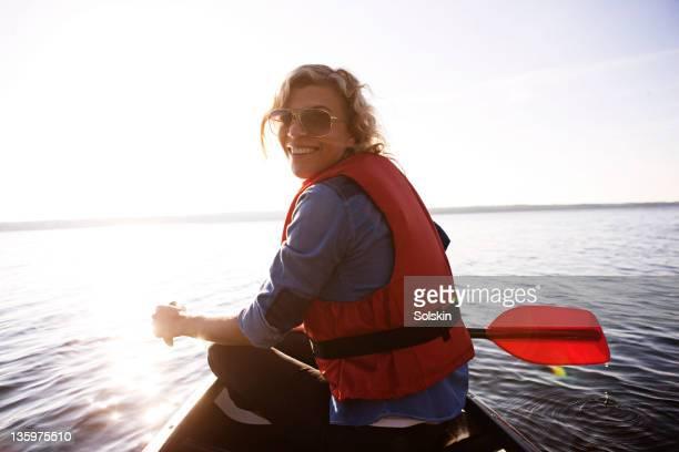 woman sitting in canoe, sailing on lake