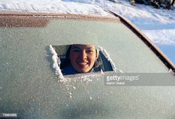 Woman sitting in car a and peeking through a frost covered windshield