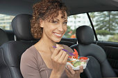 Woman sitting in car eating take out salad, smiling, portrait