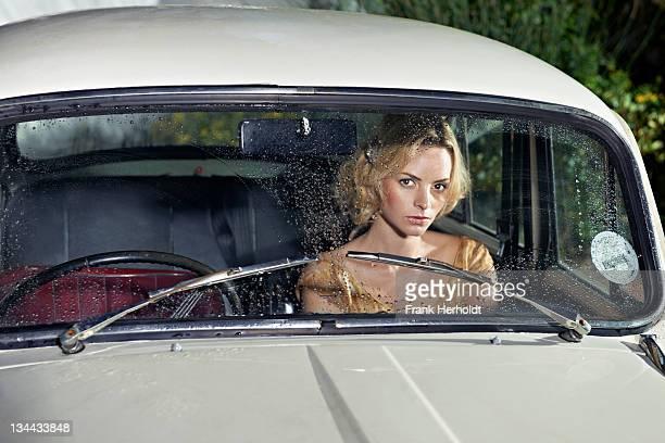 Woman sitting in car seen through rainy windscreen