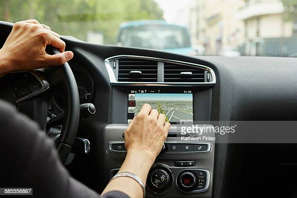 Woman sitting in car, using gps, focus on hands