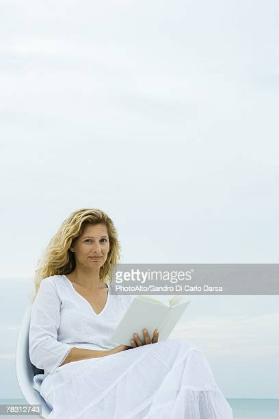 Woman sitting in chair at the beach, holding book, smiling at camera