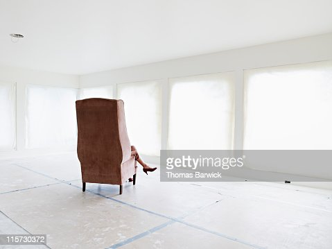 Woman sitting in chair in empty home : Stock Photo