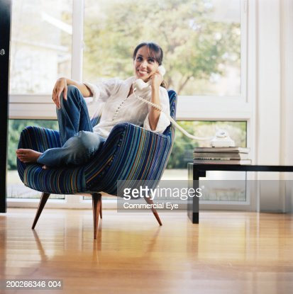 Woman sitting in chair, using phone