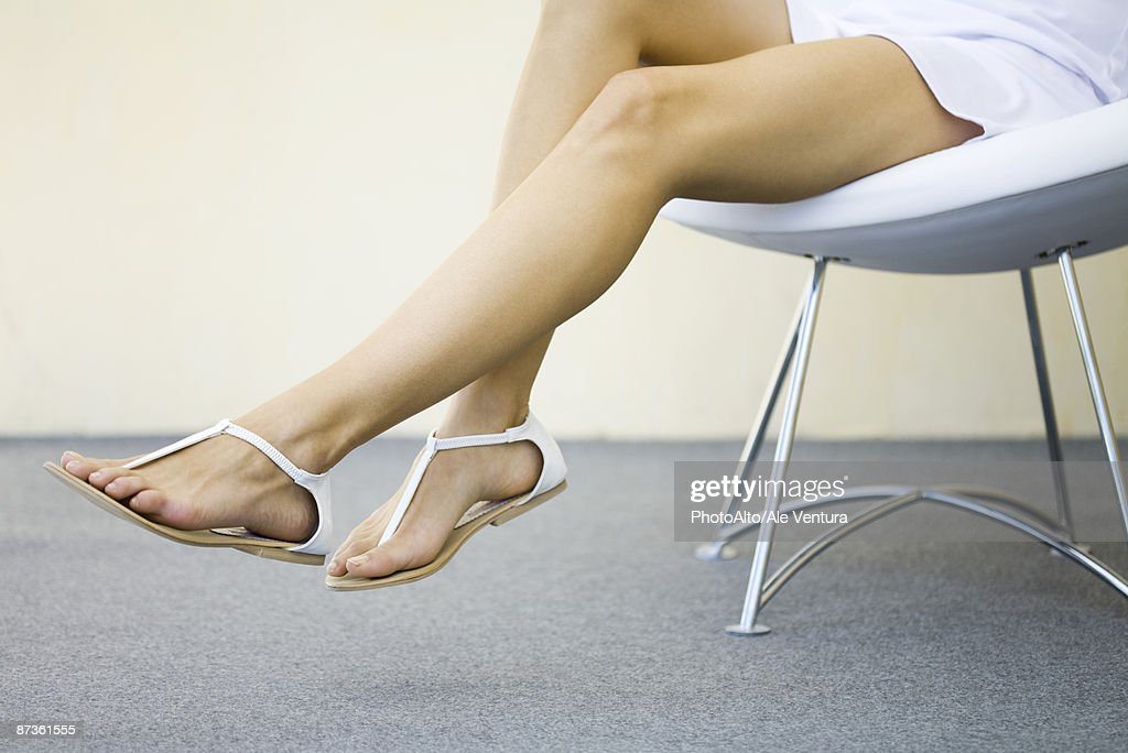 Woman Sitting In Chair With Legs Dangling Wearing Sandals ...