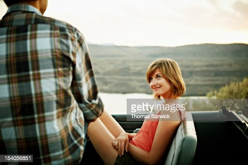 Woman sitting in convertible looking at boyfriend : Stock Photo