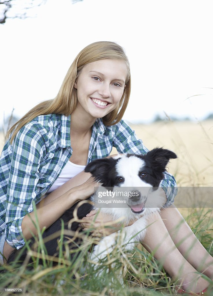 Woman sitting in countryside with young dog. : Stock Photo