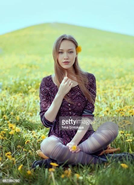 Woman sitting in dandelion field on sunny day