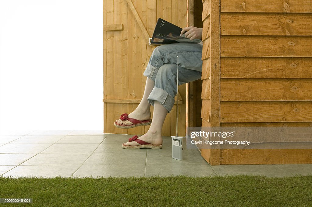 woman sitting in deckchair inside garden shed reading magazine stock photo - Garden Sheds Reading