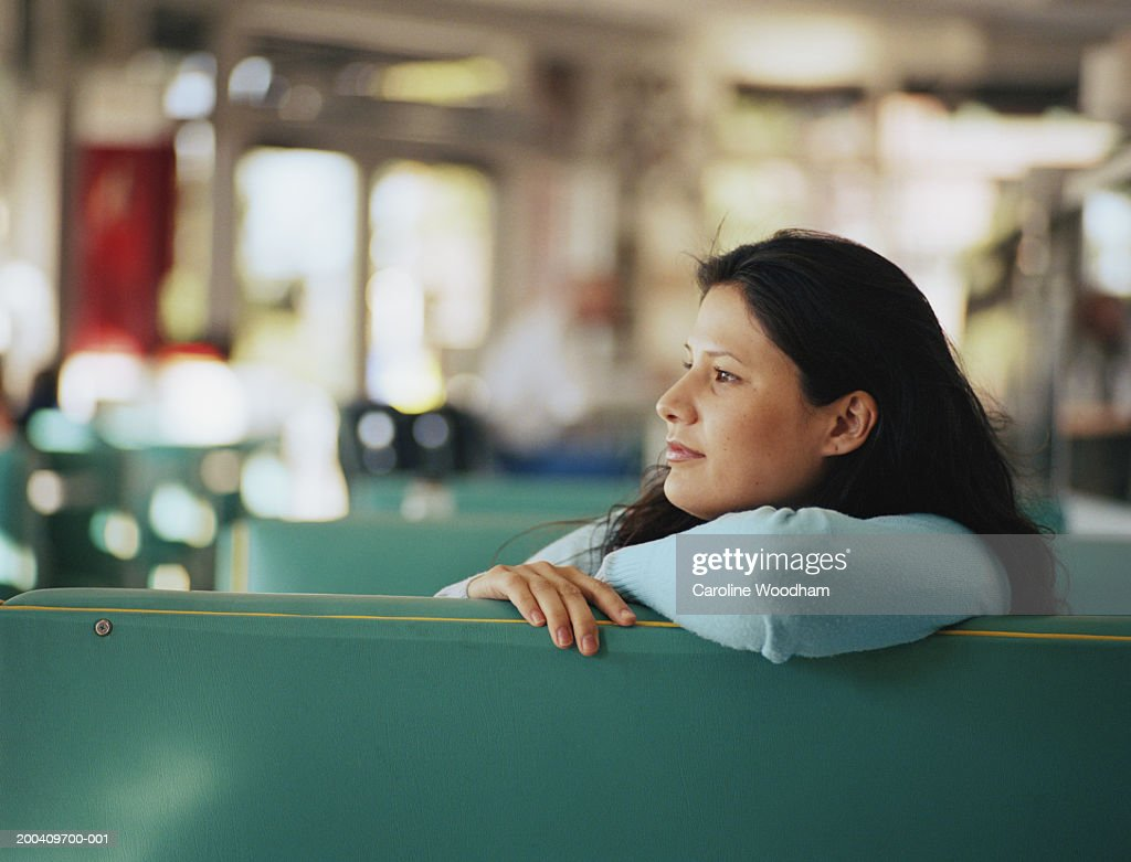 Woman sitting in diner leaning on back rest, side view, close-up : Stock Photo
