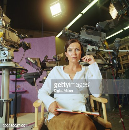 Woman sitting in 'director's chair', cameras in background, portrait