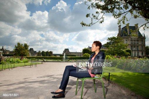 Woman sitting  in European Garden reading, Paris