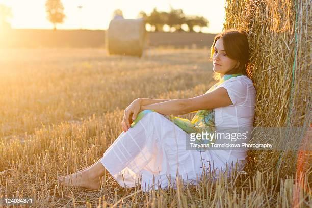 Woman sitting in field of wheat