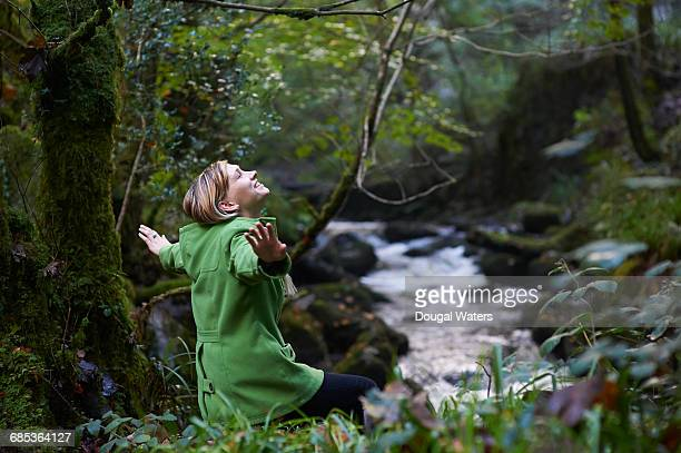 Woman sitting in forest beside stream.