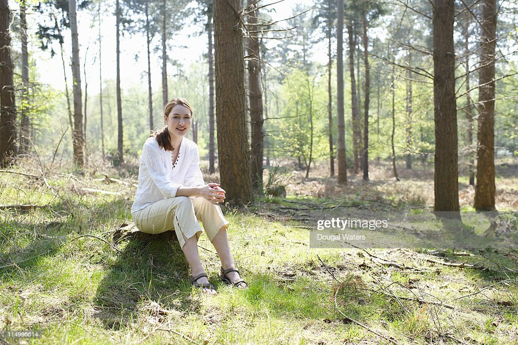 Woman sitting in forest. : Stock Photo