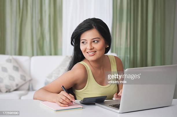 Woman sitting in front of a laptop and writing in a diary