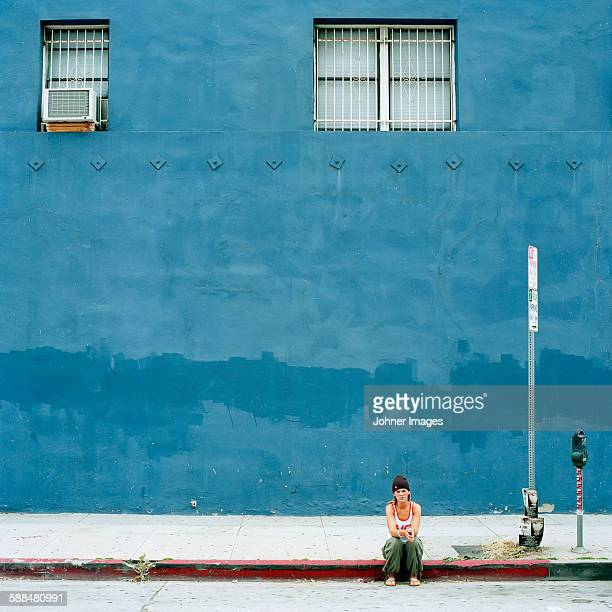 Woman sitting in front of blue building
