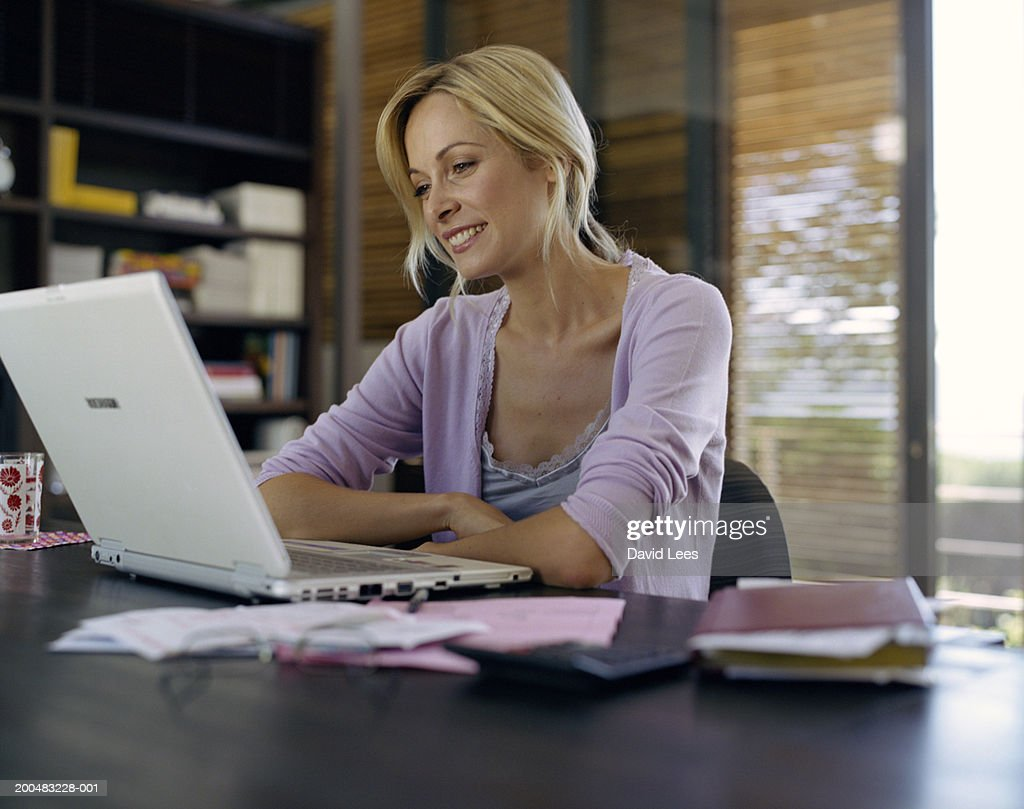 Woman sitting in front of laptop at home : Stock Photo