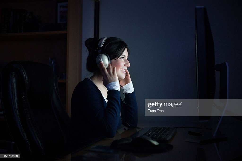 woman sitting in front of monitor with headphones : Stock Photo