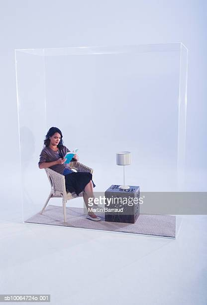 Woman sitting in glass cabinet, reading book