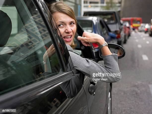 Woman Sitting in Her Car in a Traffic Jam Looking Back and Gesturing With Frustration