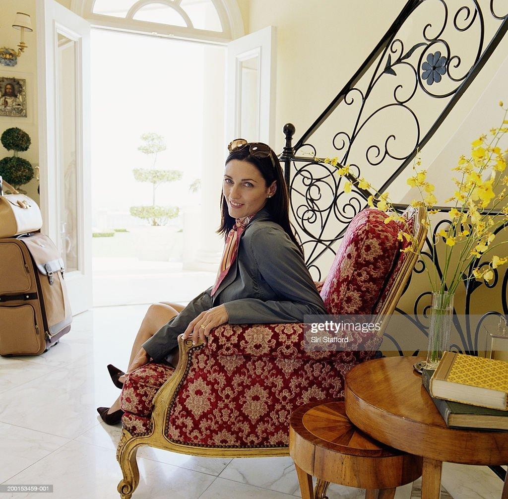 Woman sitting in hotel lobby, portrait : Stock Photo