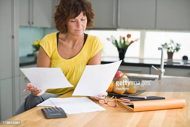 Woman sitting in kitchen with bills