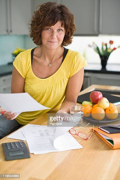 Woman sitting in kitchen with bills, smiling